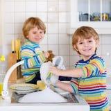 帮助在有洗涤的盘的厨房里的滑稽的双男孩 库存照片