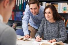 帮助在类的老师母少年学生 免版税库存图片
