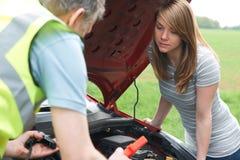 帮助失败的女性驾驶人的技工 免版税库存图片