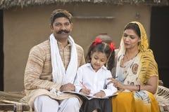帮助女儿的农村父母做学校家庭作业 免版税图库摄影