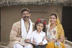 帮助女儿的农村父母做学校家庭作业 免版税库存照片
