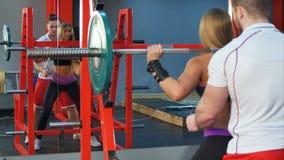 帮助女性客户举的杠铃的个人教练员在健身房 免版税库存照片