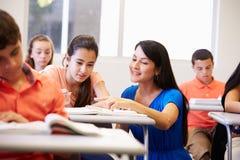 帮助女性高中学生的老师在教室 免版税库存照片