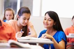 帮助女性高中学生的老师在教室 免版税库存图片