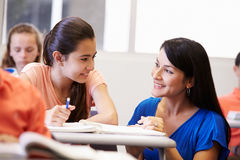 帮助女性高中学生的老师在教室 库存图片