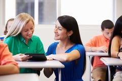 帮助女性高中学生的老师在教室 免版税图库摄影