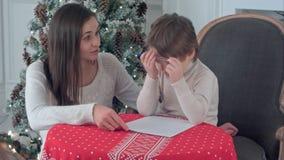 帮助她奋斗的儿子的年轻母亲给圣诞老人写信 图库摄影