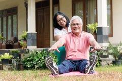 帮助她的伙伴的快乐的资深妇女在锻炼会议期间 免版税库存照片