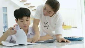 帮助她的儿子的亚裔母亲的慢动作做在白色桌上的家庭作业 影视素材