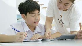 帮助她的儿子的亚裔母亲的慢动作做在白色桌上的家庭作业 股票录像