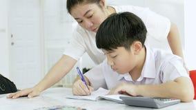 帮助她的儿子的亚裔母亲的慢动作做在白色桌上的家庭作业 股票视频