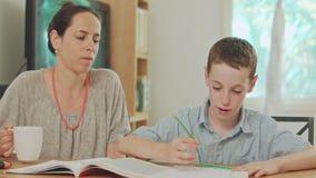 帮助她的儿子的母亲在家做他的家庭作业 影视素材