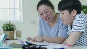 帮助她的儿子的母亲在家做他的家庭作业 股票录像