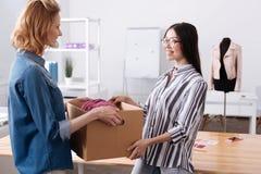 帮助她的同事的宜人的妇女运载箱子 图库摄影