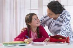 帮助她的女儿的妈妈做家庭作业 库存图片