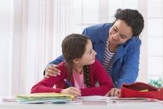 帮助她的女儿的妈妈做家庭作业 免版税库存照片