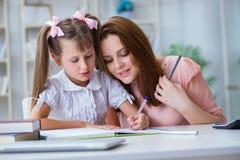 帮助她的女儿的母亲做家庭作业 库存照片