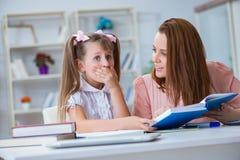 帮助她的女儿的母亲做家庭作业 免版税库存图片
