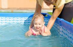 帮助她的女儿的年轻母亲游泳 图库摄影