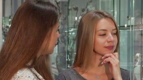 帮助她的女性顾客的女性珠宝商选择首饰买 免版税库存照片