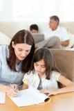 帮助她的她的家庭作业的母亲女儿 免版税图库摄影