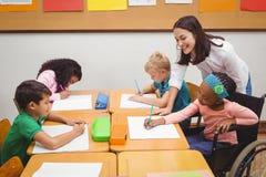帮助她的学生的愉快的老师 免版税库存图片