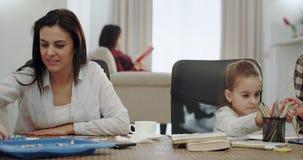 帮助她的孩子的令人敬畏的成熟母亲做学校项目,坐在一张现代客厅桌里的他们非常 影视素材