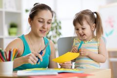 帮助她的孩子的妈妈切开色纸 库存图片