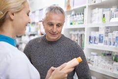 帮助她的客户的可爱的女性药剂师 免版税库存照片