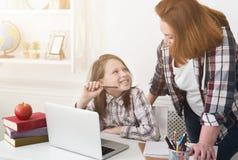 帮助她的家庭作业母亲的女儿 库存图片