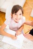 帮助她的家庭作业母亲的女儿 免版税图库摄影