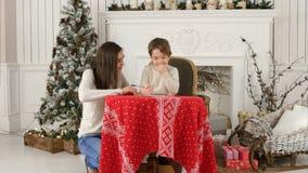 帮助她的小儿子的年轻母亲给圣诞老人写信 库存照片