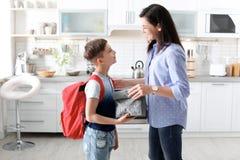 帮助她的小孩的少妇准备好学校 库存图片