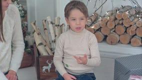 帮助她的小男孩的年轻母亲计数在他的自圣诞前夕的手指 库存照片
