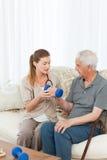 帮助她的患者的可爱的护士执行执行 图库摄影
