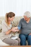 帮助她的患者的可爱的护士执行执行 免版税库存照片