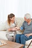 帮助她的患者的可爱的护士执行执行 库存图片
