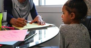 帮助她的有家庭作业的年轻母亲女儿在桌4k上 股票视频