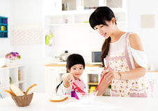 帮助她的母亲的女孩在厨房里准备食物 免版税库存照片