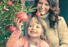 帮助她的母亲的女孩装饰圣诞树 免版税库存图片