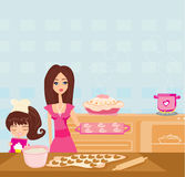 帮助她的母亲的愉快的女儿烹调在厨房里 库存图片