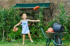 帮助她的母亲的逗人喜爱的小女孩在后院 图库摄影
