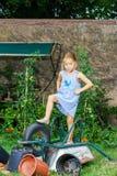 帮助她的母亲的逗人喜爱的小女孩在后院 免版税库存图片