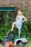 帮助她的母亲的逗人喜爱的小女孩在后院 免版税图库摄影