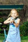 帮助她的母亲的逗人喜爱的小女孩在后院 库存照片