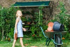 帮助她的母亲的逗人喜爱的小女孩在后院 免版税库存照片