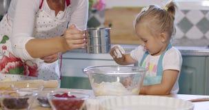 帮助她的母亲的逗人喜爱的小女孩烘烤馅饼 股票视频