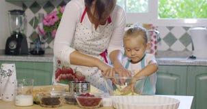 帮助她的母亲的逗人喜爱的小女孩烘烤 股票视频