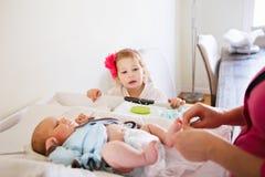 帮助她的母亲,改变的婴孩尿布的逗人喜爱的女孩小孩 免版税库存图片