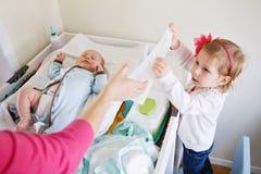 帮助她的母亲,改变的婴孩尿布的逗人喜爱的女孩小孩 库存照片